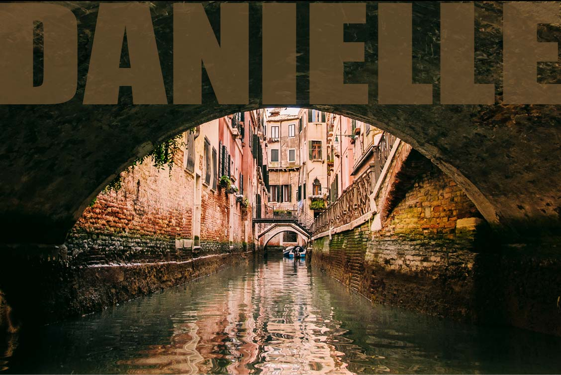 The arch of a centuries old bridge frames a Venice canal scene